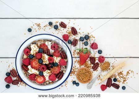 Healthy fresh breakfast concept with granola, pollen grain, yoghurt, berry fruit, nuts with foods high in protein, omega 3, anthocyanins, antioxidants, minerals and vitamins. Top view.