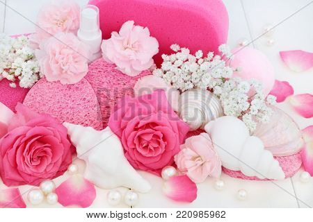 Beauty treatment cleansing and spa products with pink roses and carnation flowers, seashell soaps, bath bomb, body lotion, seashell soaps, sponges and decorative pearls.