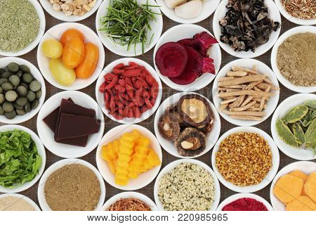 Brain boosting health food selection with fruit, vegetables, bee grain pollen, seeds, dark chocolate, supplement powders with herbs also used in herbal medicine.
