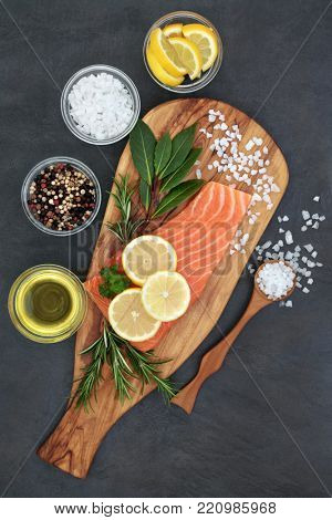 Fresh salmon fish with herbs, seasoning, olive oil and lemon fruit on marble slab on slate background. Healthy heart food high in omega 3 fatty acids.