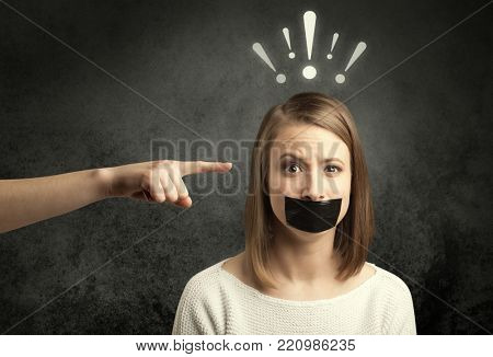 Caucasian hand pointing at female employee with drawn exclamation marks above her head