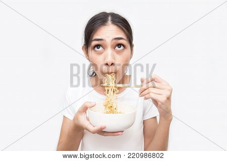 Young Beautiful Asian Woman Eating Yummy Hot And Spicy Instant Noodle Using Chopsticks Isolated On W