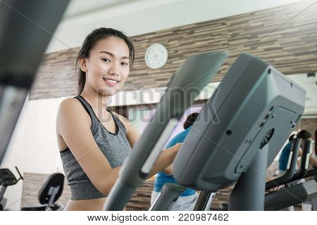 Attractive Young Asian Tan Woman Runs On A Treadmill Air Walk, Asian Beautiful Girl Is Engaged In Fi