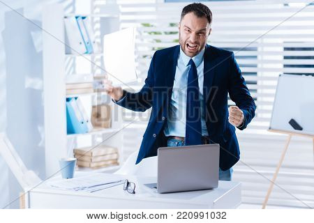 Feeling angry. Angry young emotional businessman standing in his big light office and feeling furious while holding unsatisfying documents in his right hand