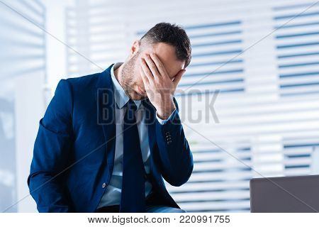 Oh no. Emotional hardworking businessman sitting in his office and feeling upset when closing his eyes after facing a misfortune at work