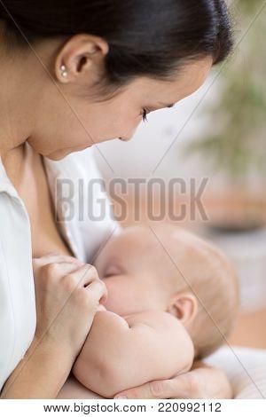 Young mom holding her newborn child. Mom nursing baby. Pretty woman breast feeding kid.