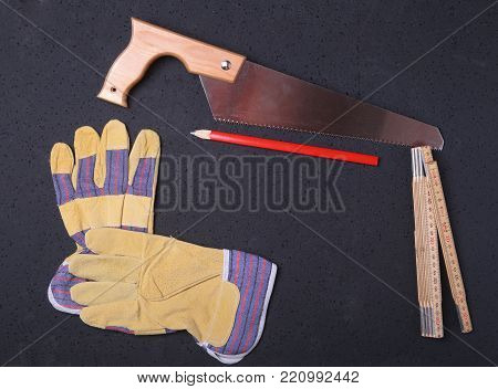 Orange hard hat, safety glasses, gloves, saw and measuring tape on wooden background. you can place your text.