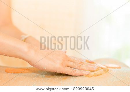 Spa therapist hand is scrubbing salt scrub on to a woman back