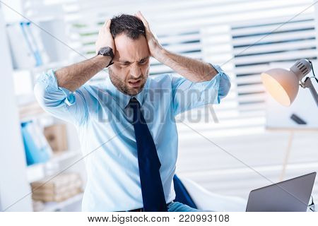 Horrible mistake. Expressive young worker feeling irritated and angry while standing with his hands pressing his head and understanding his silly mistake in a very important document