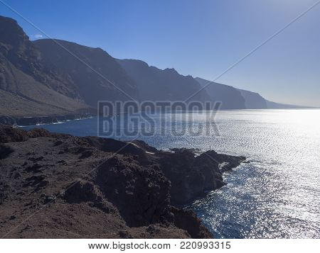 view on hight lava cliffs los gigantes on Punta de Teno cape on west Tenerife canary island with lava rock blue sea and clear summer sky Contre-jour against daylight