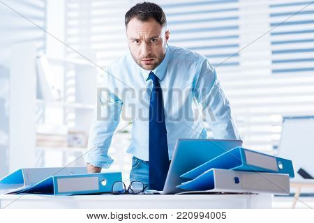 So unfair. Young clever qualified worker feeling at a loss while being in a big light office and standing near the table covered with blue folders after being dismissed poster