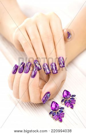 beautiful purple manicure with earrings on the white wooden table.