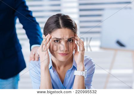 Headache. Young tired upset woman touching her head while being at work and having a terrible headache