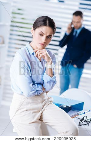 Bad day. Young clever emotional woman feeling unsatisfied with her working day and looking gloomy while sitting on the table in her big office