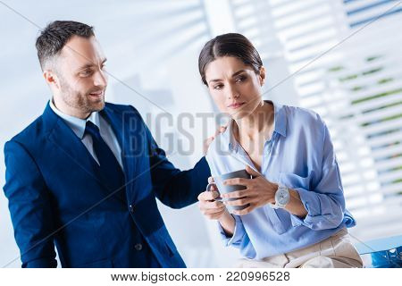 Smiling colleague. Cheerful kind attentive man touching the shoulder of his upset young colleague while looking at her sitting with a cup of tea
