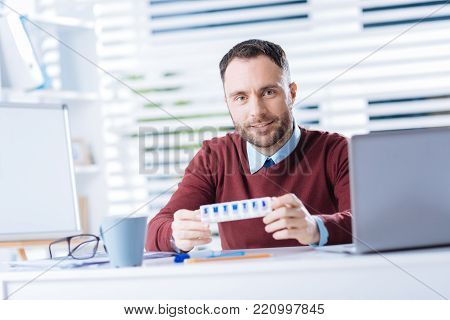 Useful thing. Cheerful positive young man smiling while sitting in his comfortable office in front of a laptop and holding a useful little pillbox after recovering from illness