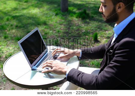 Person using laptop and clicking keyboard, putting hands up, close computer and goes away. Boy has beard and short hair. Guy dressed in black jacket, white jeans and blue shirt. Concept of modern technologies new apps on laptop online work for freelancer.
