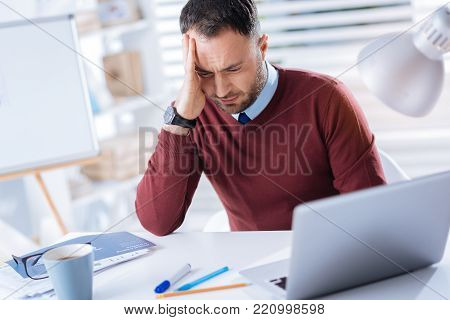 Feeling dizzy. Tired young unhappy man sitting at the table in his big office and touching his head while having strange feelings in it