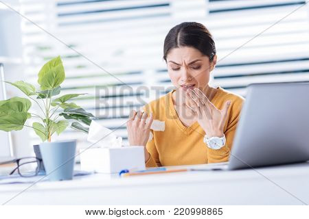 Sneeze. Beautiful young desperate woman feeling unwell while being ill and constantly sneezing when trying to work in her office