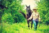 Animal and human love, equine concept. Western woman walking on green meadow or forest with horse poster