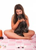 smiling brunette teenage girl in swimsuit at the beach kissing her shipoo dog (studio setting with beach items and little stones) isolated on white background poster