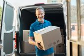 Proud delivery man in blue uniform holding parcel and looking at camera. Smiling mature courier standing in front of cargo van delivering package. Portrait of delivery man holding card box. poster