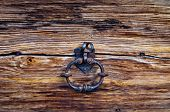 knocker in burnished metal of an ancient wooden door poster