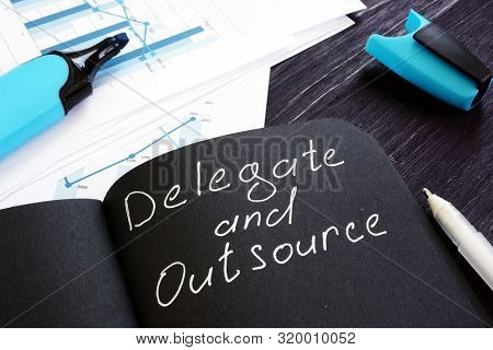 Delegate And Outsource Written On A Black Page. Delegation Cincept.