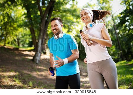 Young People Running Outdoors. Couple Or Friends Of Runners Exercising In Park