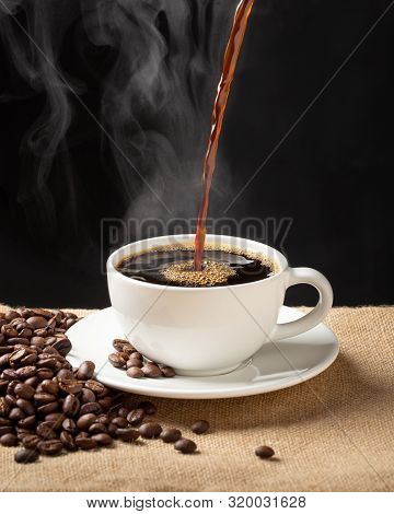 Cup Of Steamy Coffee With Smoke And Coffee Beans. Hot Coffee On Black Background.