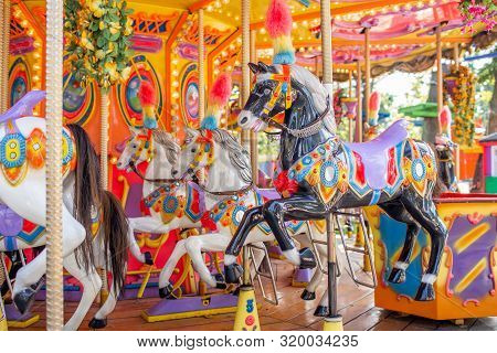Old French Carousel In A Holiday Park. Three Horses On A Traditional Fairground Vintage Carousel. Me