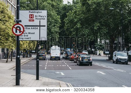 London, Uk - July 18, 2019: Cars Drive Park Directional Road Signs On A Street In London, Uk, Motion