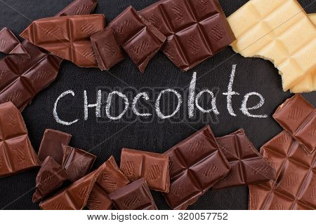 Chalk Inscription Chocolate And Chocolate Bars. Different Chocolate Pieces And Chalkboard With Inscr