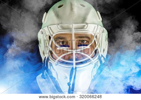 Detail Of A Male Face In A White Goalie Hockey Mask And  Blue And White Smoke.this Is A Detail Hocke