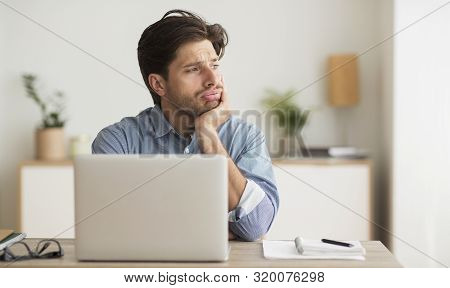 Boring Job Concept. Man Sitting Bored At Laptop In Office. Free Space For Text