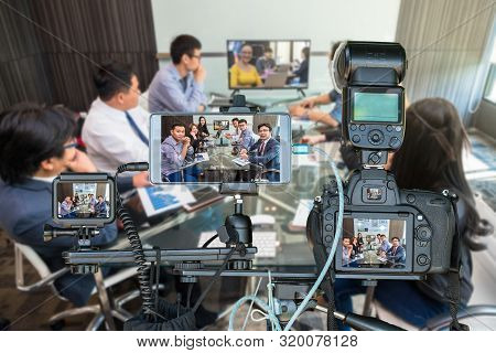 Professional Set Of Camera With Smart Mobile Phone And Action Camera On Tripod Over Group Of Asian B