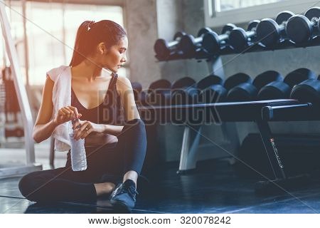 Fit Young Woman Sitting And Resting After Workout Or Exercise In Fitness Gym. Woman At Gym Taking A