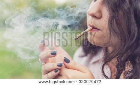 Girl Smoking Medical Marijuana Joint Outdoors, Close-up. Cannabis Is A Concept Of Herbal Medicine.