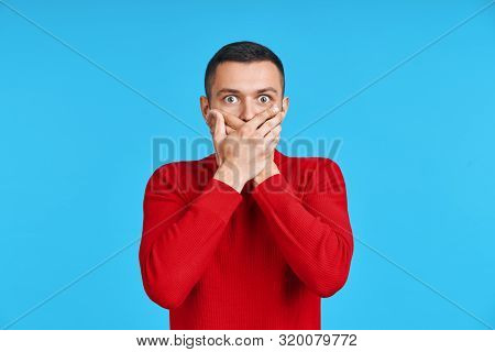 Shocked Man Covering Mouth With Hands Over Blue Background. Emotions And Secret Concept