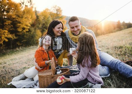 A Young Family With Two Small Children Having Picnic In Autumn Nature At Sunset.