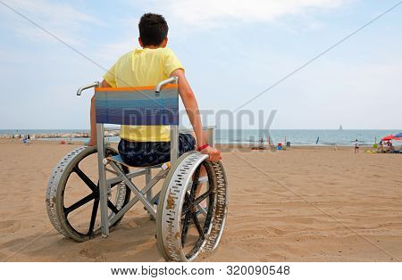Disabled Boy On A Wheelchair On The Beach Admires The Sea