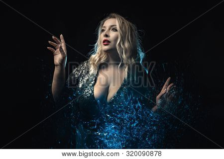 Close-up plus size model in decollete shiny dress. Light effect. Black background. Young woman wearing the shiny dress with sequins those reflect the light tracks. Inspiration expression. Fashion shot