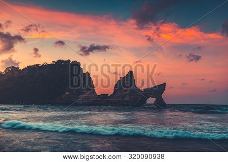 Beautiful Natural Rock Arch in Ocean Water. Bright colorful sunset sky. Atuh Beach in Nusa Penida a small island near Bali, Indonesia