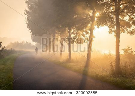 Cyclist In The Fog On The Towpath Along The Lys In Lauwe - Menen, Belgium. After A Cold And Clear Ni