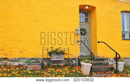 Yellow Brick House Entrance With Seasonal Wreath On Door And Porch Window On Autumn Day With Fall Le
