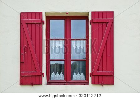 Sunny View Of A Red Window Of An Old Farm House With Shutters, Where A Curtain Of Handmade Crochet H