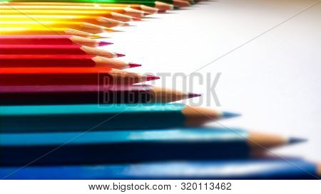 Colored Pencils Arranged Horizontally. Some Are Blurred While A Few Are Not. They Are Sharpened And