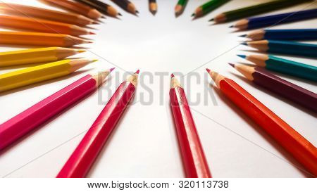 Colored Pencils Arranged In A Circle With Spacing In Between Them.they Are Sharpened And Pointy