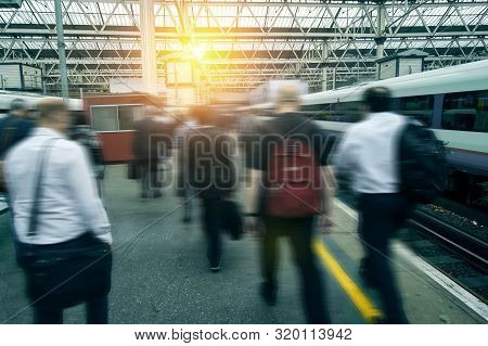 Rush Hour At The Train Station. People Commuter Walking. Blurred City Workers And Business People Go