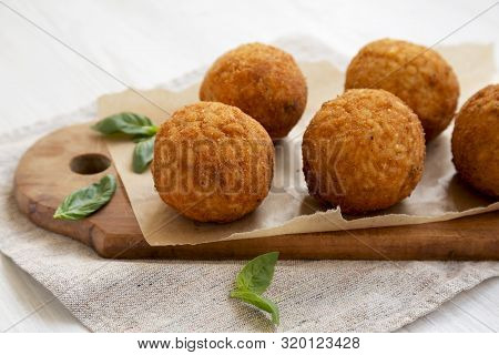 Homemade Fried Arancini With Basil On A White Wooden Background, Side View. Italian Rice Balls. Clos